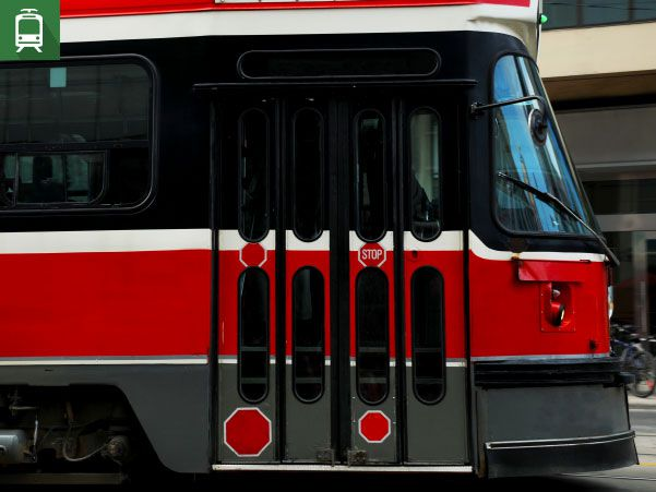 A red, white, and black Toronto Transit Commission (TTC) streetcar