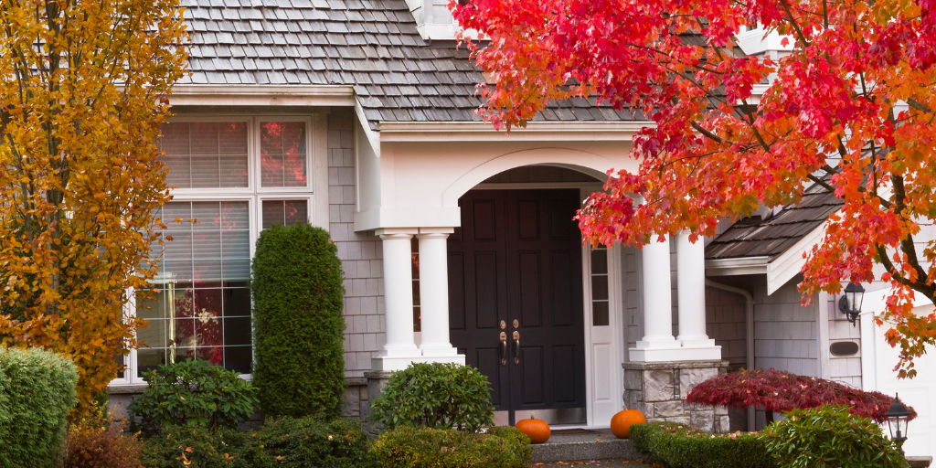 the exterior of a home in the fall with trees with bright orange leaves