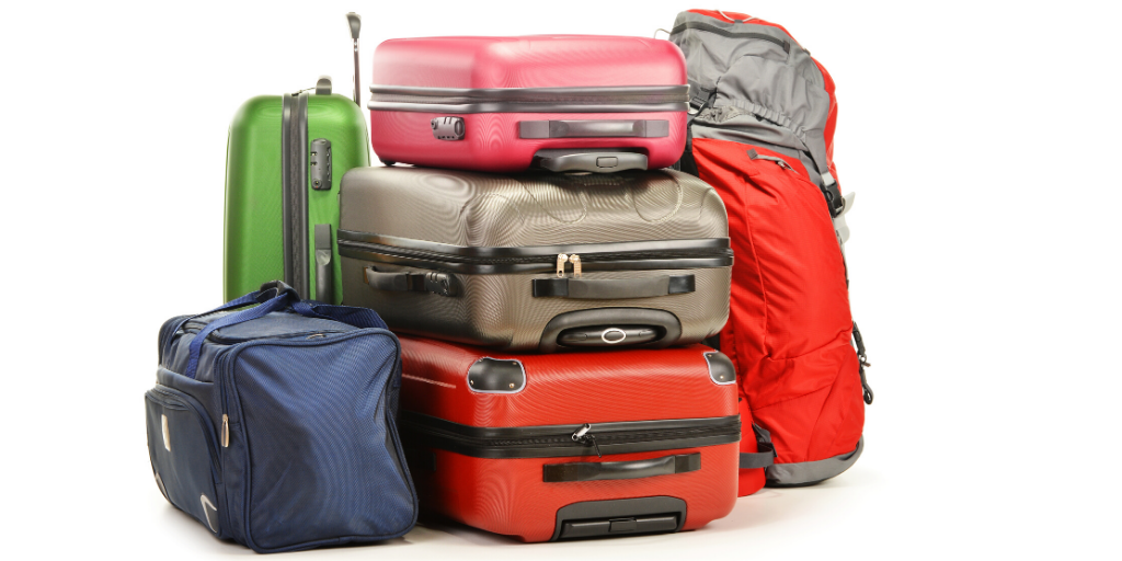 a pile of different coloured suitcases