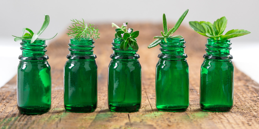 green bottles of herbs on a wooden table.