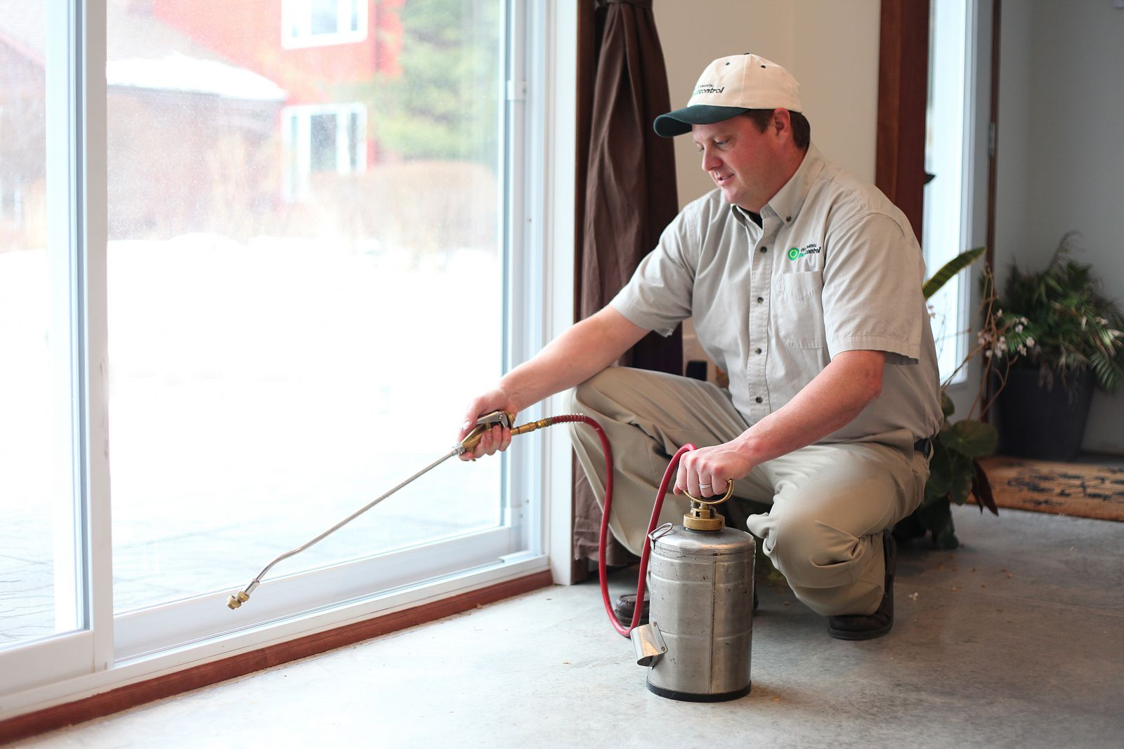 Licensed Pest Control Professional Applying Treatment Indoors