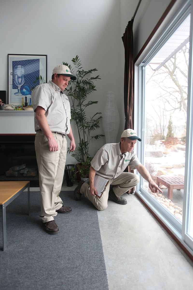 Licensed Pest Control Professionals Assessing Pest Infestation Indoors
